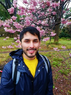 Photo of the author in Japan in front of a cherry blossom tree