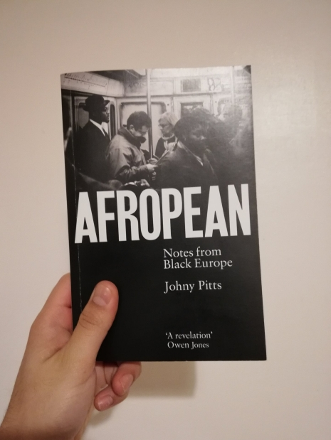 A hand holding a copy of a book, Afropean by Johny Pitts.