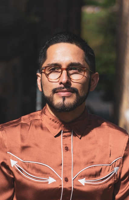 A photo of a man wearing a silk western cowboy style shirt in a copper brown. He wears brown glasses and has short black cropped hair and a thick black beard. He is looking skyward and the sun is shining on him.